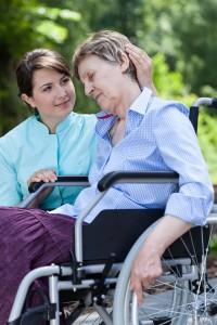Nurse hugs an elderly disabled woman